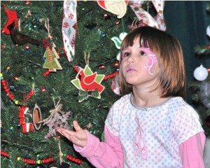 After getting her face painted, Violet Thomas, 4, checks out the trees.
