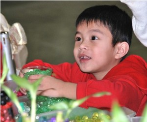 Davinci Chin, 5, scoops a jar of water beads in the festival's crafts section.