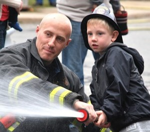 Firefighter Eric Jusseaume assists Benjamin Bostrom, 4, aim toward a mock burning house.