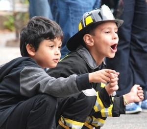 Ariel Simoes and Richard DeMoura, both 6, are amazed watching firefighters demonstrate a vehicle extraction.