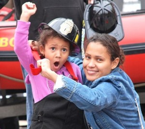 Maria Victoria, 4, gets into a junior firefighter uniform with help from her mother, Diolene Rodrigues.
