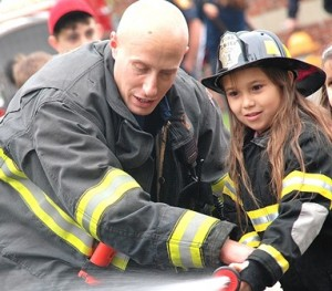 Firefighter Eric Jusseaume helps Tarcia Rocon, 7, operate a fire hose.