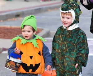 Quinn Torpey, 2, dressed as a jack-o-lantern, and Evan Greengo, 4, as a dinosaur, spot the store where they'sl get their next treats.