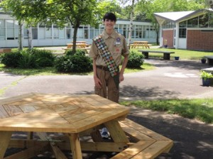 Justin Friess shows off one of the four tables he and his team made for his Eagle Scout service project at the Whitcomb Middle School.  Photo/submitted