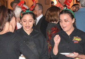 Donning reindeer antlers, Jasmine Benites and Yugely Galicia are served a seafood dish from Marlborough's Kennedy's Restaurant & Market. Photos/Ed Karvoski Jr.