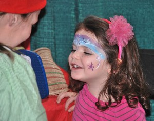 Nora Finocchario, 3, is pleased to see the reflection of her painted face.