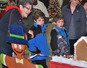 Carol Passerello and her grandsons Cole Beninati, 8, and his brother Max, 6, view entries in the gingerbread house contest.