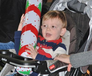 Mason Campbell, 2, clutches an inflatable candy cane that he won at the duck pond game.