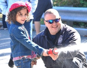 Karlina Alcoba, 5, aims a fire hose toward a mock burning house with help from Firefighter Bryan D'Antonio.