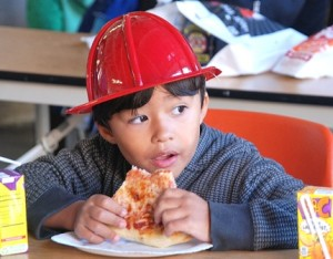 Thalles Assis, 4, munches pizza while watching an educational video hosted by Sparky the Fire Dog.