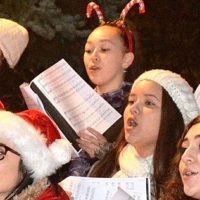 Holiday gear accessorizes some chorus singers' musical performance.