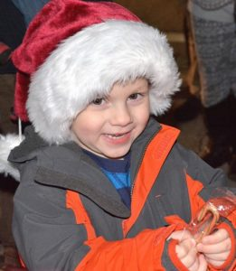 Sam Blumenthal, 5, is happy to get a candy cane from Santa Claus.