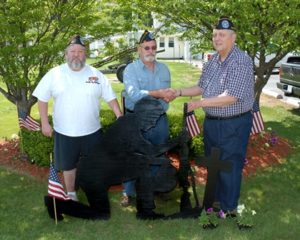 Fellow veterans and members of the Italian American Veterans Post 45 of Marlborough, Mike Durand (l) commander of the Sons of the ITAM and John Kortes, commander of the ITAM, (r ) express their appreciation to member John Dupree, (center), who made a Soldier's Prayer Shadow cut-out for the group. Photo/John Sahagian