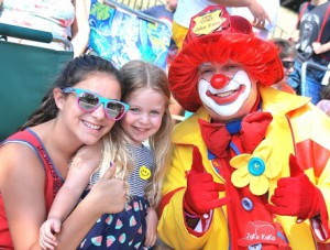 (l to r) Elizabeth Grasso, 12, and her cousin Lilly Chiasson, 4, meet Joko Koko of the Aleppo Shrine Clowns along the parade sidelines.