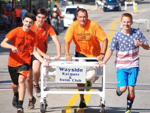 Racing toward first-place victory in 1:53 is the team sponsored by Wayside Racquet & Swim Club, consisting of (l to r) Marlborough High School Cross Country runners Owen Crisafulli, Tom Redden, Coach Jeff Downin and runner Jeremy Barnes.