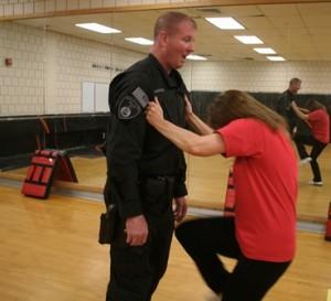 Sue Blaisdell practices a knee strike on Officer Ken McKenzie at the Rape Aggression Defense Program at Marlborough High School. (Photo/Bill Shaner)