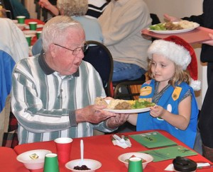 Jim Fay is served dinner by Madelyn Glynn, 6, of Girl Scout Daisy Troop 78138, during a Dec. 3 gathering at the Marlborough Senior Center. Photo/Ed Karvoski Jr.