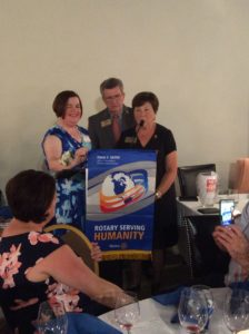 "(l to r) President Peggy Sheldon receives the Rotary International theme banner from Rotary District 7910 governors Francis ""Skip"" and Pat Doyle. (Photos/submitted)"