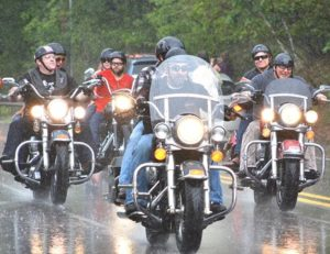 Motorcyclists begin the seventh annual Shawna Jean Larassa Memorial Motorcycle Ride during a sudden downpour.