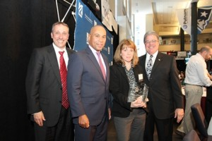 (l to r) Bryan Morry, executive director of the Hall at Patriot Place, Governor Deval Patrick, Massachusetts STEM Teacher of the Year Kelly Powers from the Advanced Math and Science Academy Charter School, and UMass President Dr. Robert Caret.