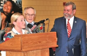 George Whapham (center) is congratulated by state Reps. Danielle Gregoire and Carmine Gentile.