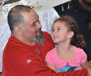 """Angelo Ayala shares a smile with his daughter Mirren, 4, while listening to the story """"Love You Forever."""""""