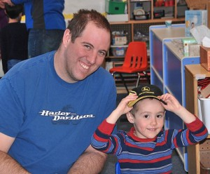 Eric Baum lets his son Joseph, 4, try on his hat.
