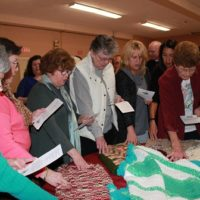 Attendees at the reception prayed over the completed shawls before donation.
