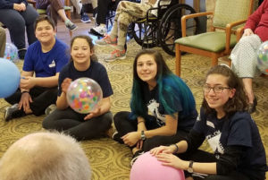 Zachary and Caitlyn Gogan and Emma and Aline Kaledjian pause in their balloon volleyball game with seniors during their recent mission trip.