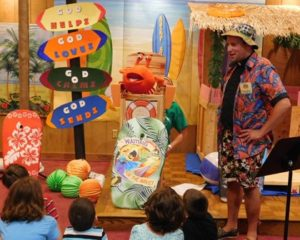 """""""Pastor Joe"""" talks to campers and the camp mascot, a crab named Snappy (aka Dianne Bruno of Hudson). Photo/Barbara Parente"""