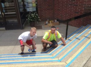 William Goliger helps the Department of Public Works paint the stairs to the Senior Center.