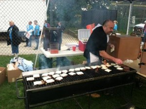 A volunteer cooks up burgers at last year's Convoy of Hope event in French Hill. (Photo/submitted)