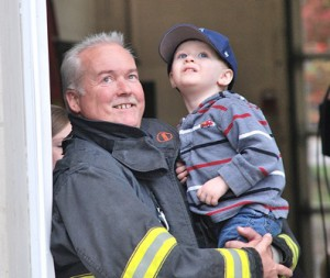 Firefighter Bill Taylor and his grandson Caleb, 2, watch a demonstration of a hook and ladder fire truck.
