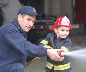 Firefighter Josh Clement assists Cole Coffin, 4, aim toward a mock burning house.