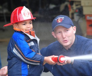 Myles Lamb, 3, learns to operate a fire hose with help from Firefighter Dana Soroka.