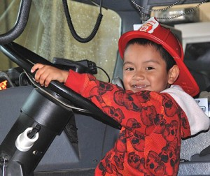 Jailen Avalos, 4, gets behind the seat of a fire truck.