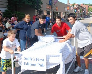 Past President Marlene King (second from left) instructs the winning team sponsored by Sully's First Edition Pub – (l to r) Marcus Chrisafideis, 10, and 16-year-old friends Nick Coppola, Jason Plaurt and Michael Sullivan