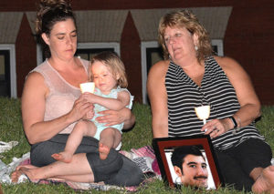 A photograph of Mikey Valerio, who died of an overdose at age 22, is brought to the candlelight vigil by (l to r) his sister Heather Blinn with her daughter Julianna, 1-1/2, and his mother Anne Valerio. Photos/Ed Karvoski Jr.