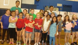Science fair participants pose with Rahi and Amol Punjabi in front of their poster boards.