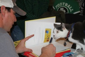Author, firefighter, and Toto's owner Jonathan Hall signs books while Toto looks on. Toto also had a stamp made of his paw print so he can sign all the books, too.