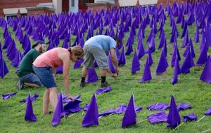 Volunteers place flags on the lawn of the Walker Building.