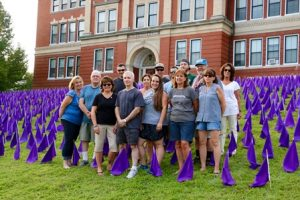 Volunteers pose for a photo after placing over 1,000 flags on the lawn in front of the Walker Building.