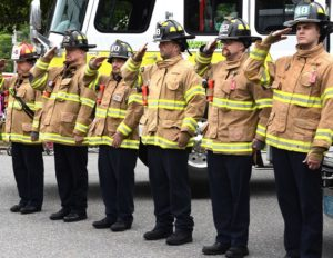 Firefighters salute as a color guard passes the station.