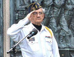 Ceremony emcee Gerard Bourque salutes as the American flag rises at the World War I Monument.