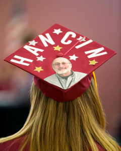 A graduate honors retiring art teacher George Hancin with decorations on her mortarboard. Photo/Jeff Slovin
