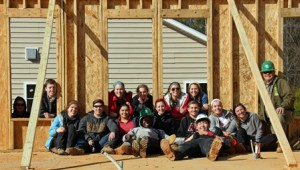 Polanowicz, (second from right, back row) leans through a newly cut out window in one of the walls she and her group constructed over her spring break. (Photos/submitted)