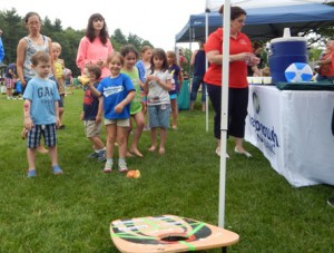 Six year old, Grace Huggins tries out the bean bag toss to win a prize from the Marlborough Savings Bank.