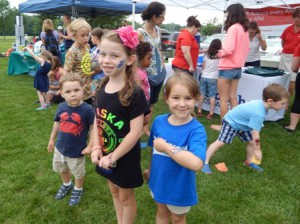 Seven year old Megan McCormick (middle) and Grace Huggins show off their glitter tattoos.  Three year old Jake Huggins (on left) waits for a turn at the bean bag toss.
