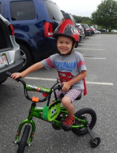 Four year old Northborough resident Miles Carlson rides his bike around the park during the concert.