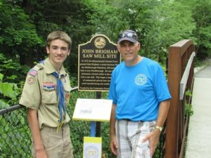 (l to r) Boy Scout Carter Brannon and Northborough 250th Committee member Norm Corbin at Marker #22 at the John Brigham Saw Mill Site where Howard Brook crosses Whitney Street.